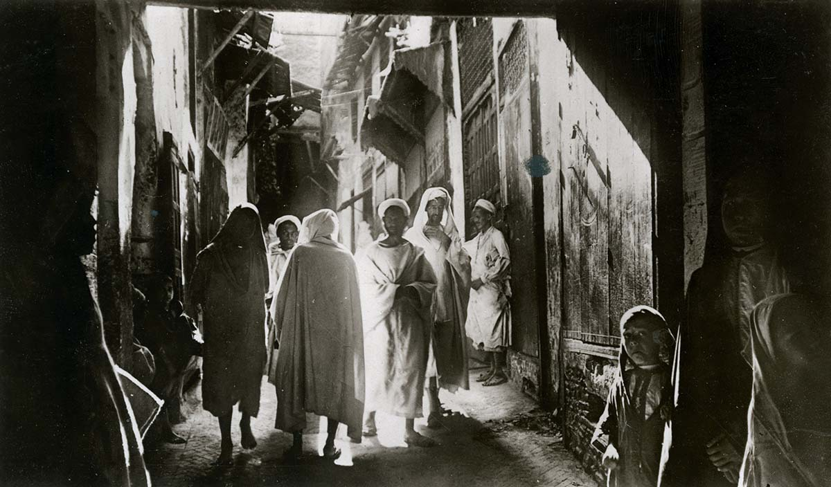 a black and white photo of a people moving through a shaded souk in Morocco