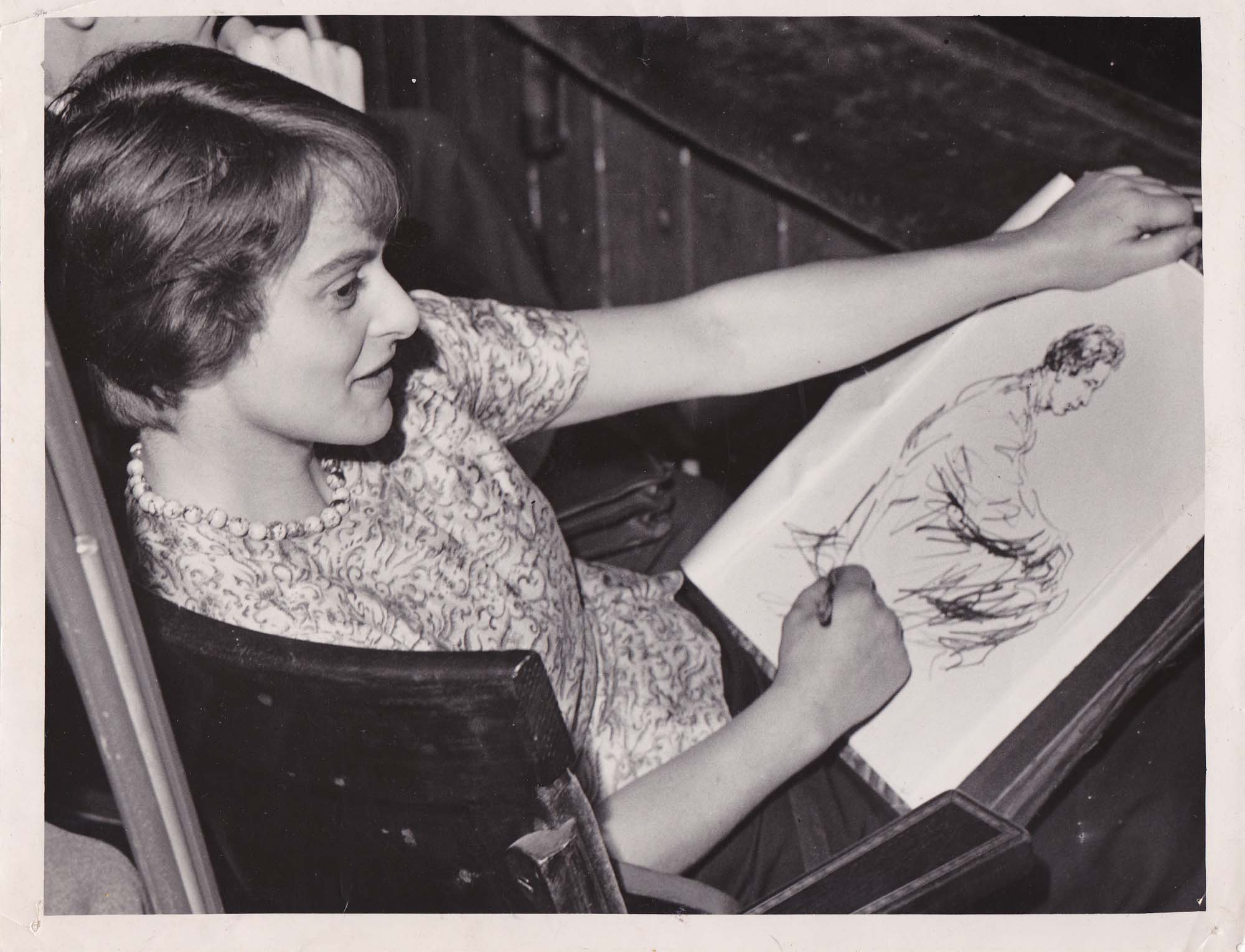 a photo of a woman reclining and sketching a man