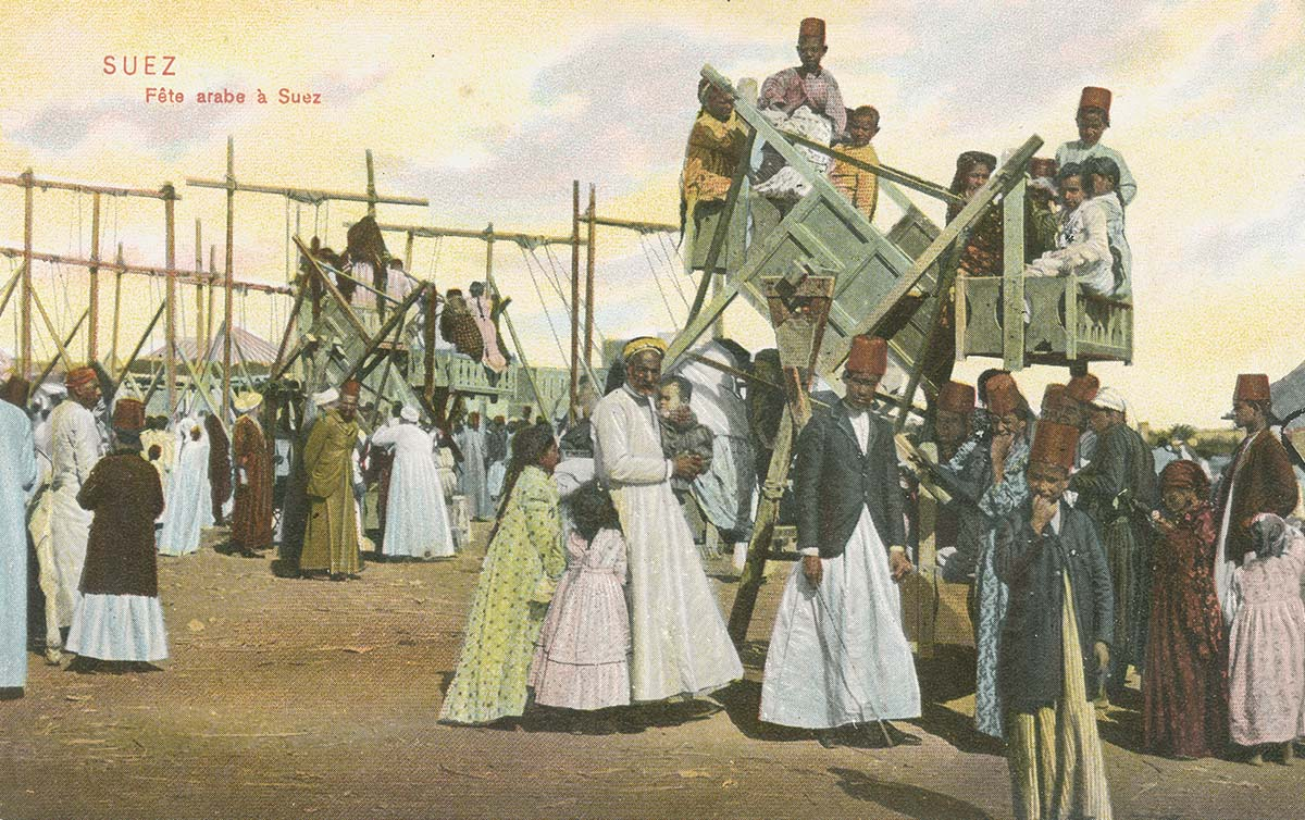 a colourised postcard showing a fete in Suez with many people wearing turbans and children sitting in wooden rides on stilts