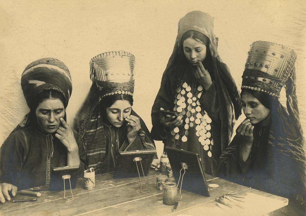 a black and white photo showing four Uzbek women in traditional dress and headgear applying make up to their faces
