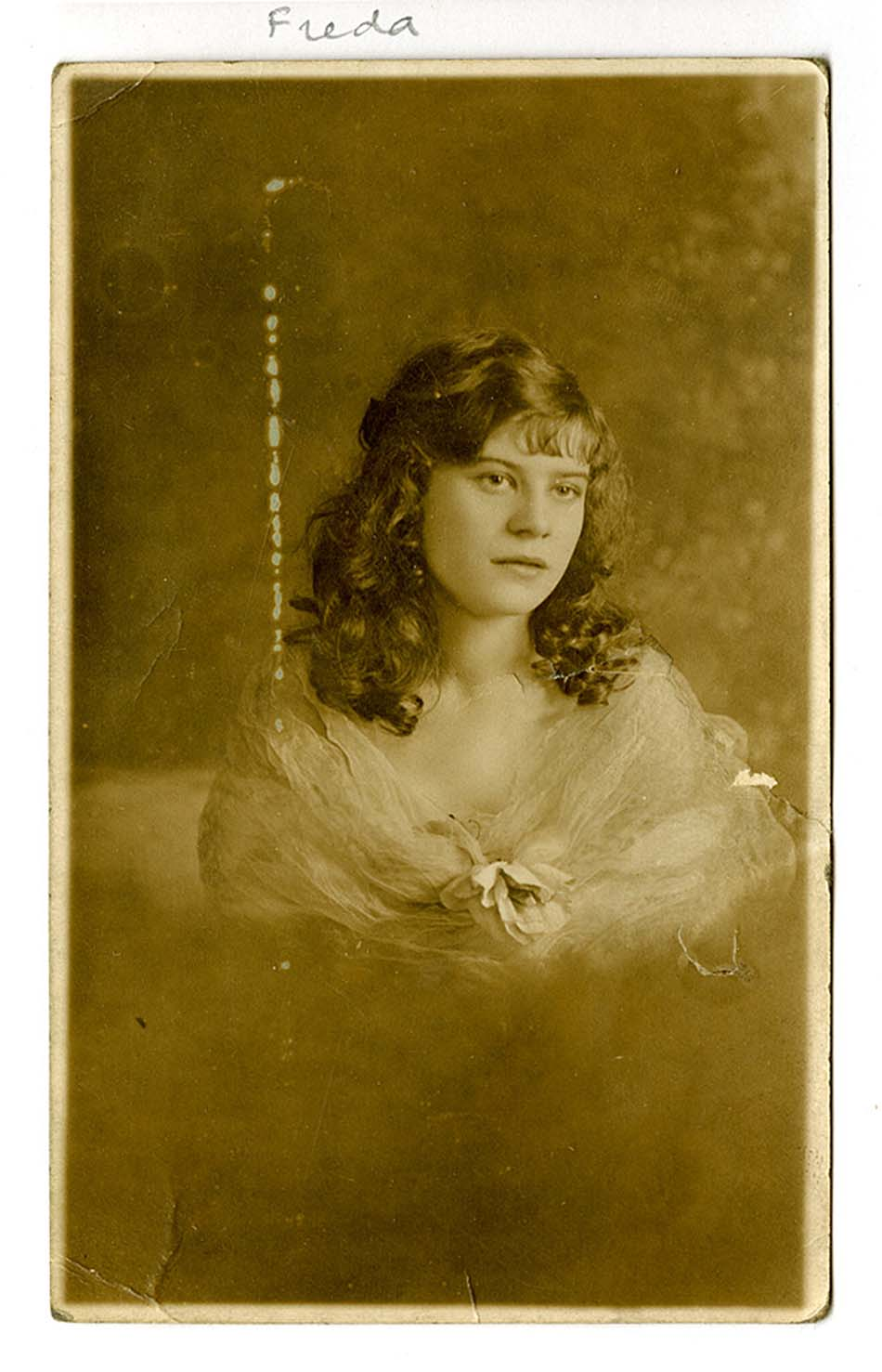 an old photograph of a young woman with curls and a taffeta shawl