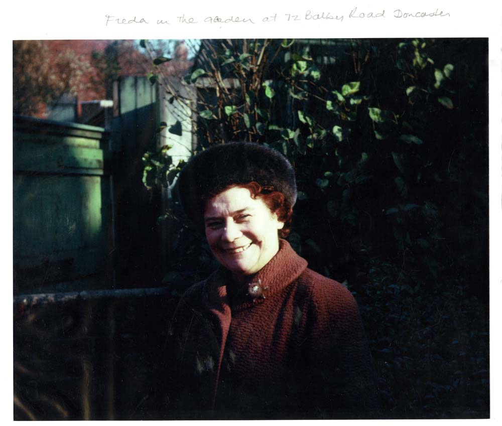 a photo of a smiling woman wearing a red winter coat and fur hat in a garden