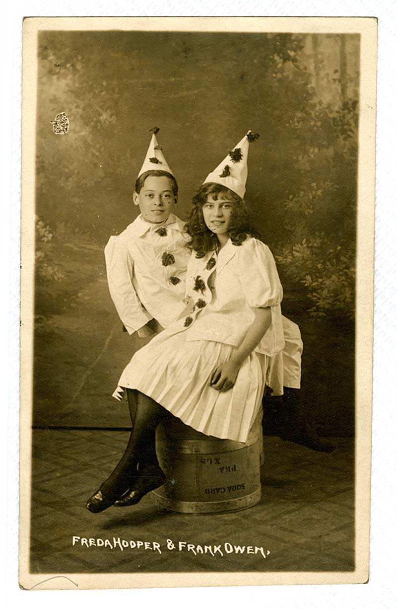 a postcard showing a teenage girl and boy in Pierrot style clown hats