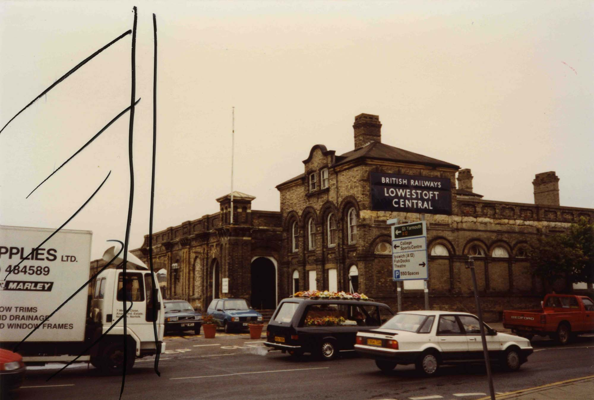 a photo of a railway station on a dreary day with cars including a hearse with a coffin in it moving along a street in front