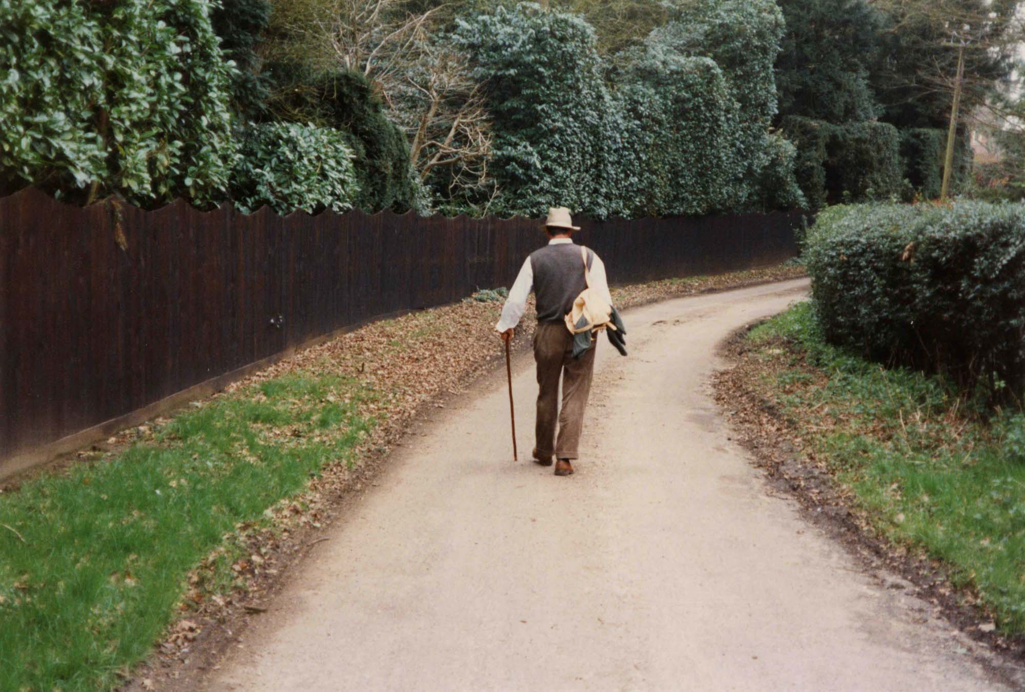 a photo of a man with a walking stick, fedora and cords walking down a path strewn with leaves