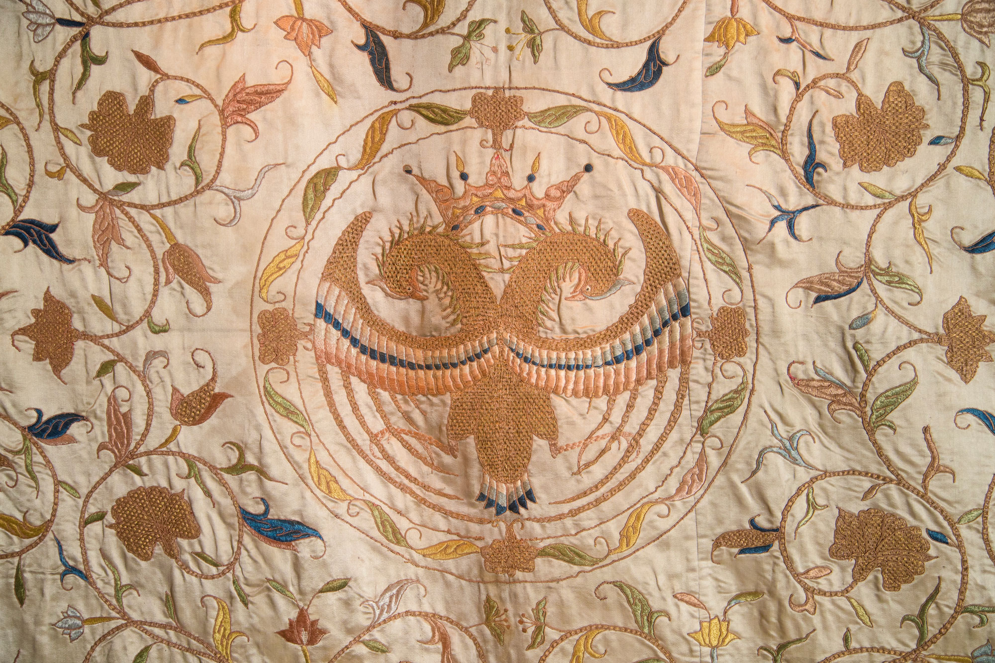 close up photograph of embroidered animal and foliage on sheet of fabric
