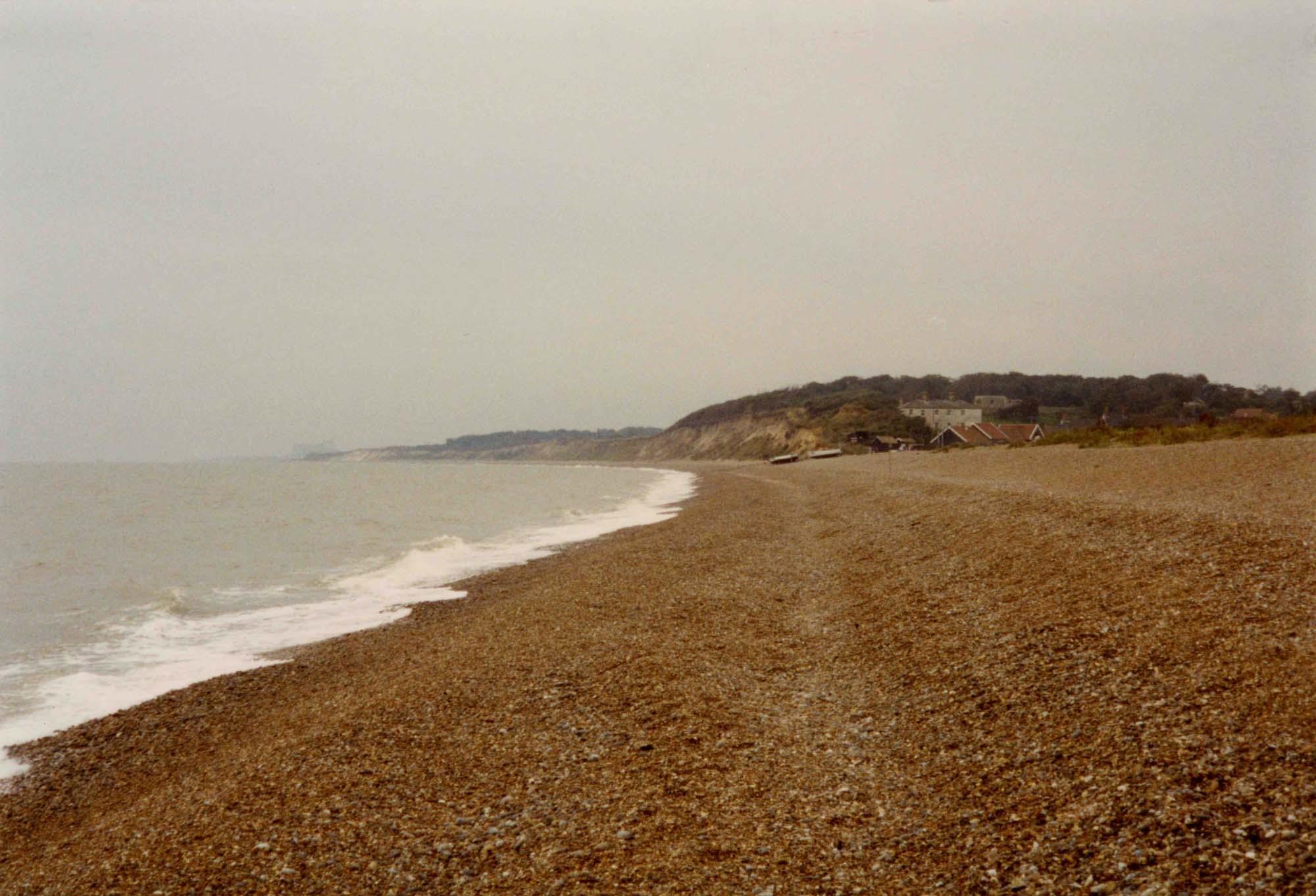 a photo across the shore of a shingle beach towards a headland