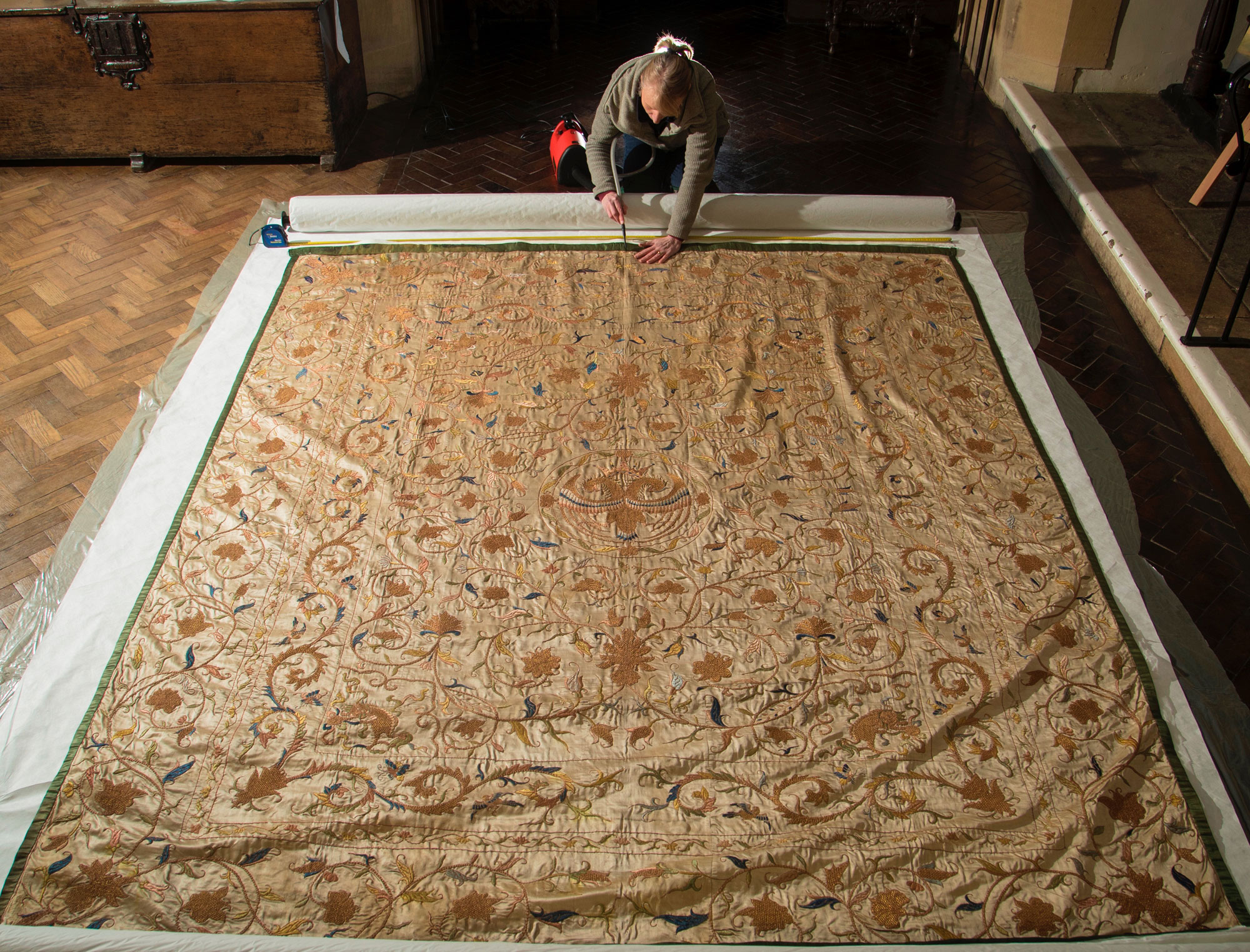 person carefully cleaning section of large golden bedspread with small vacuum cleaner