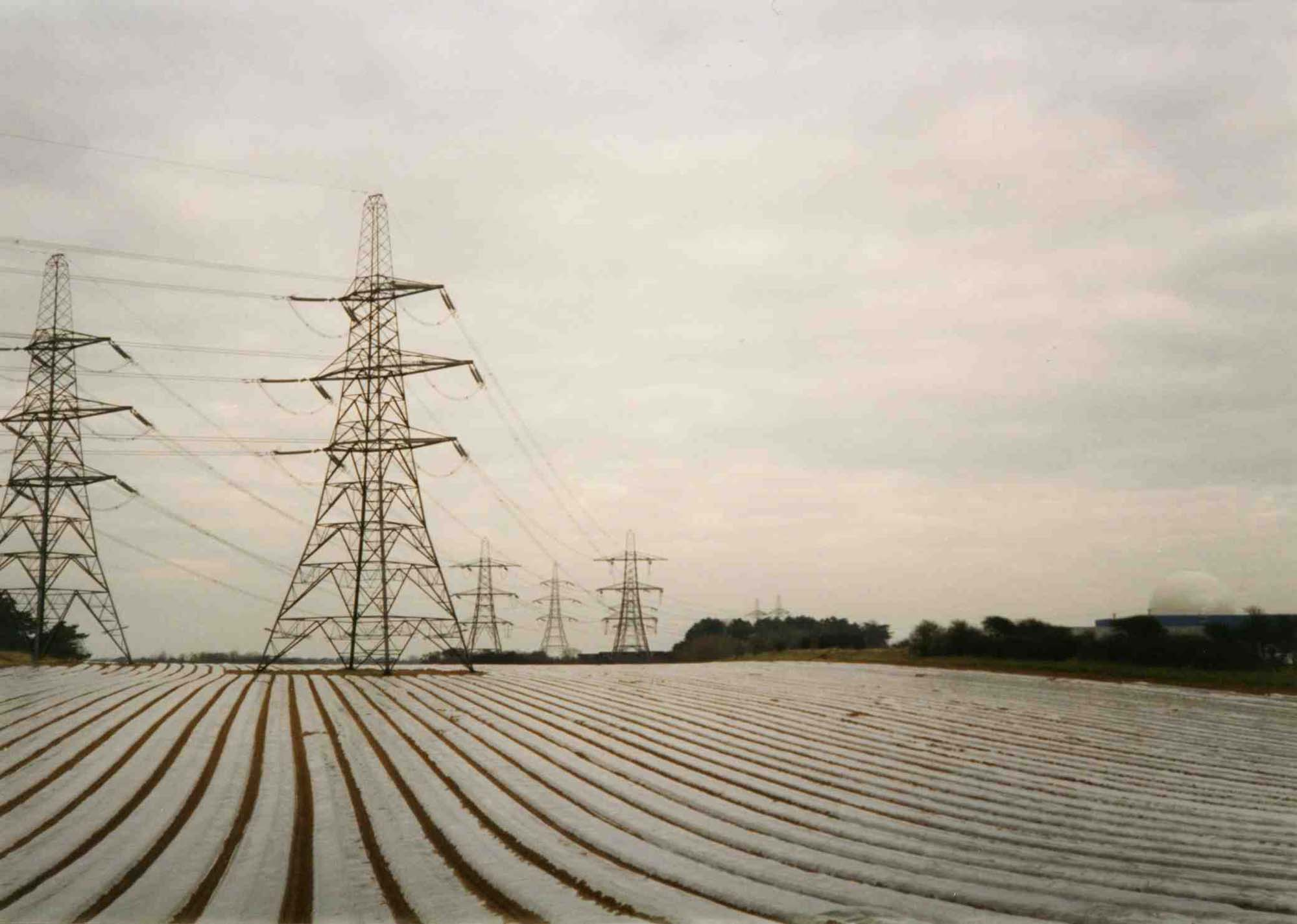 a photo looking across fields towards electricity pylons