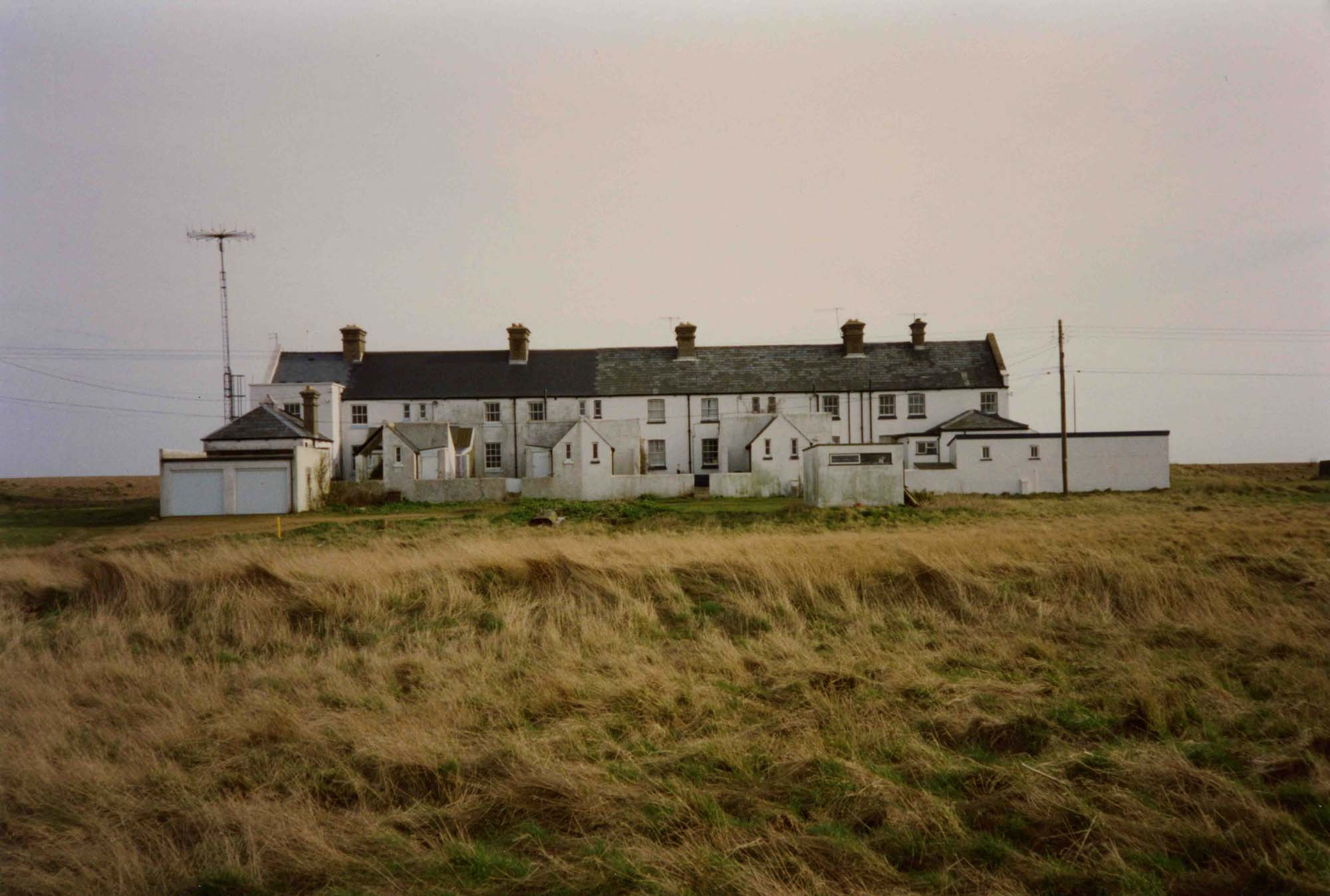 a photo of a row of white house seen across a flat fields