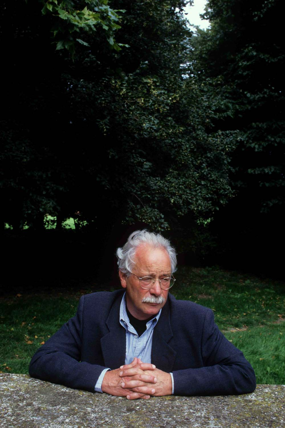 a photo of a tanned man with grey hair, glasses and moustache wearing a blazer and blue shirt with cravat seated outside
