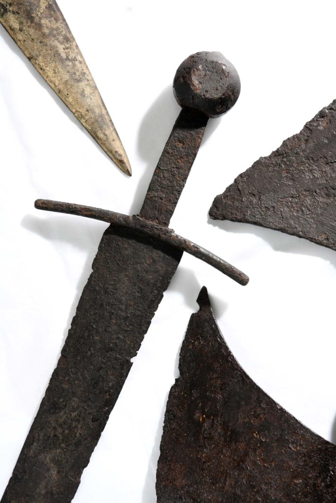 a photo of an assemblage of relic swords and other weapons