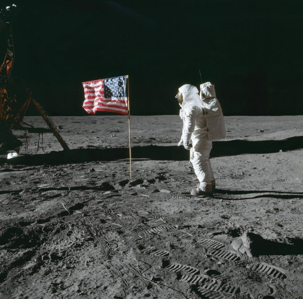 Photograph of astronaut facing an american flag on the moon