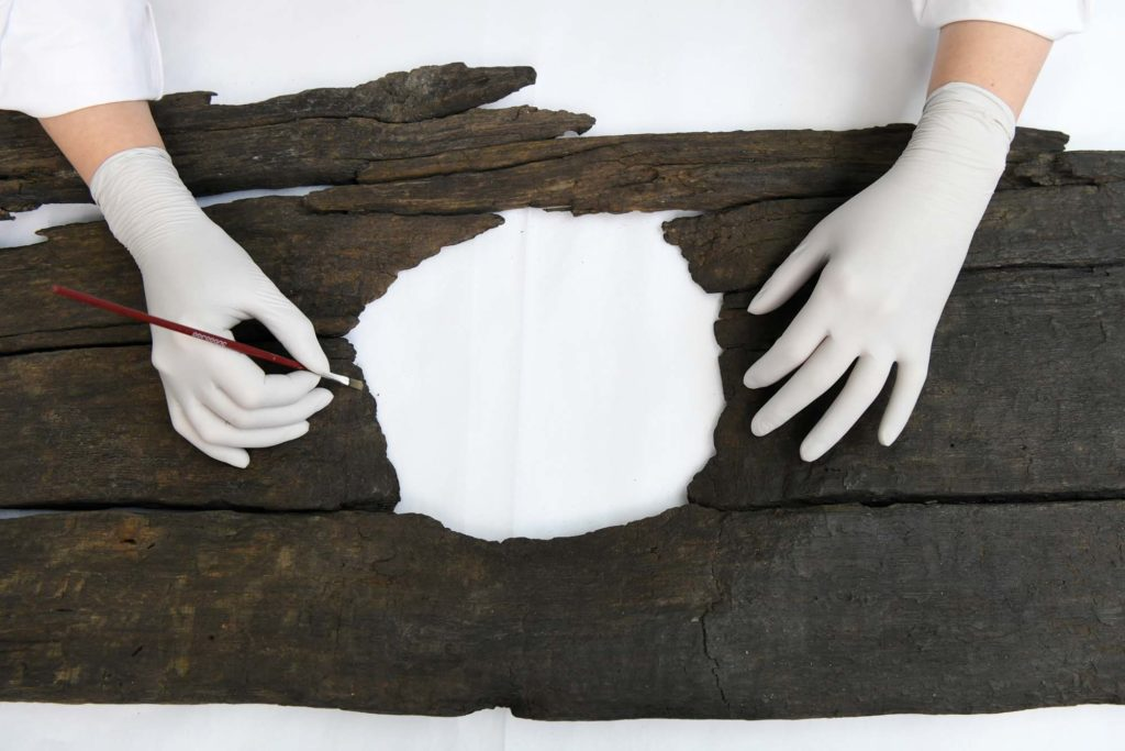 a photo of two gloved hadns resting on a piece of old wood with a round bum-sized hole in it