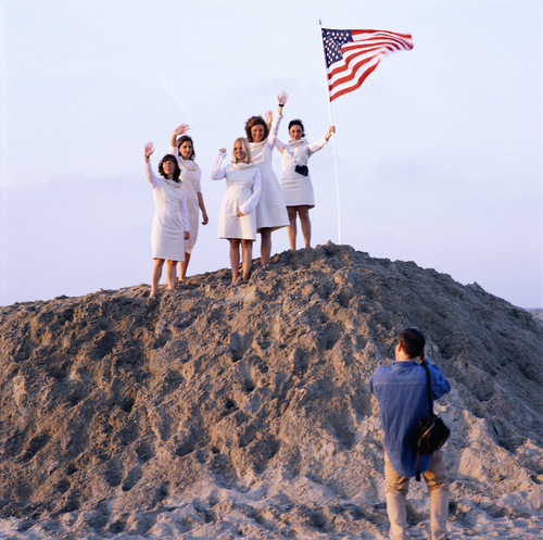 photograph of group of women in white standing at the top of a large rock with an american flag in it
