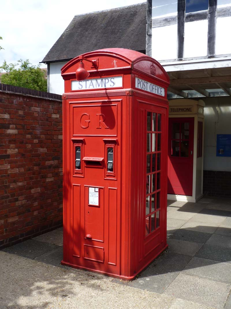a photo of a red telephone box with stamps dispenser on the outside