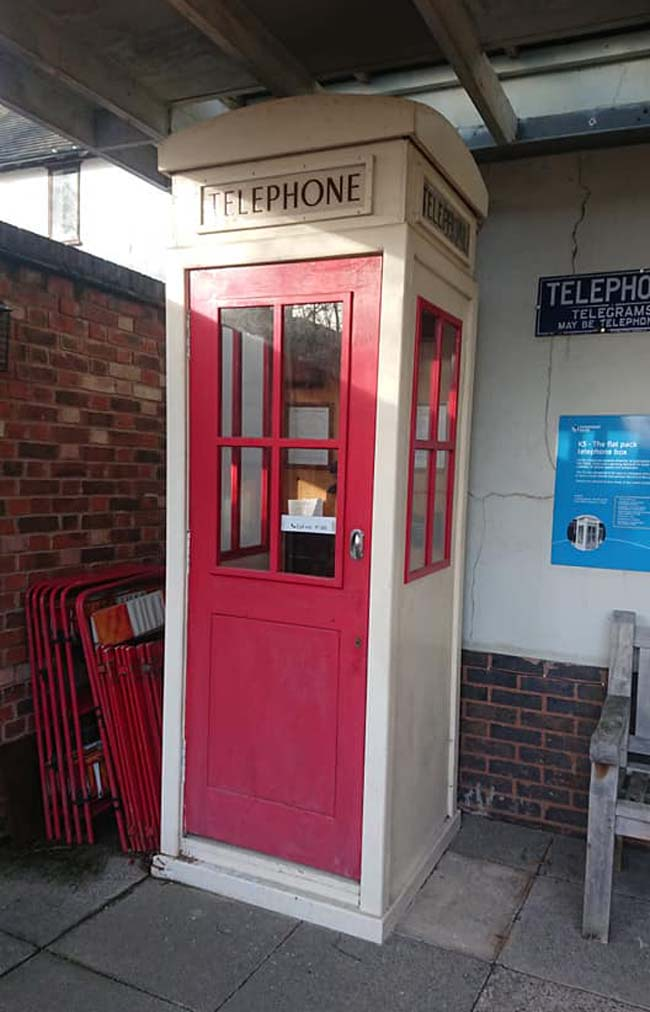 a photo of a red and white telephone box