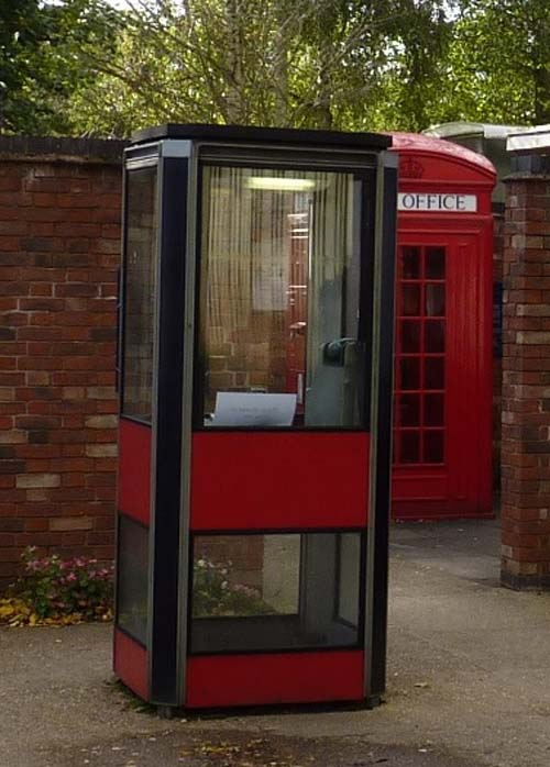 a photo of a glass and plastic telephone kiosk