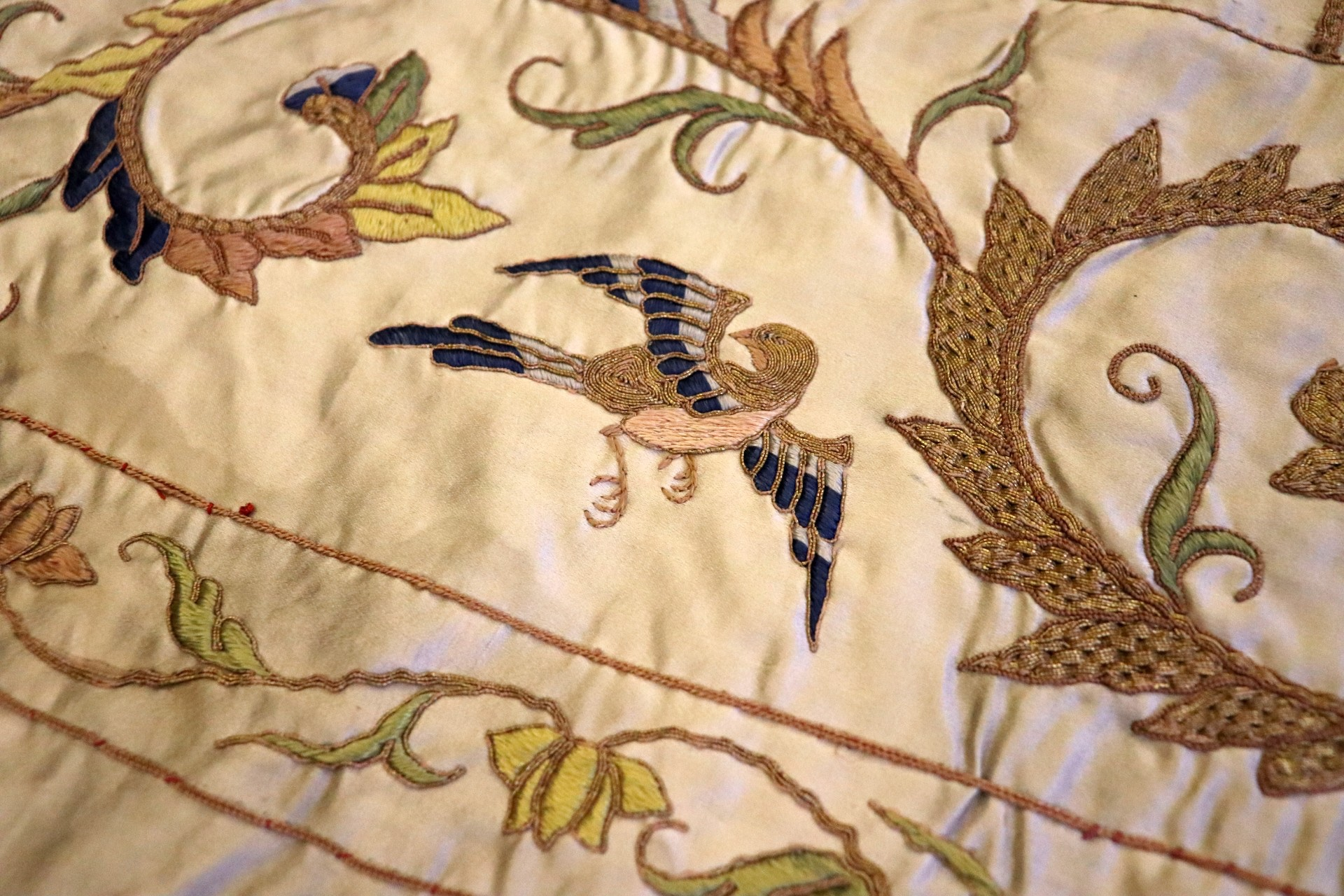 close-up photograph of embroidered bird and foliage on sheet of fabric