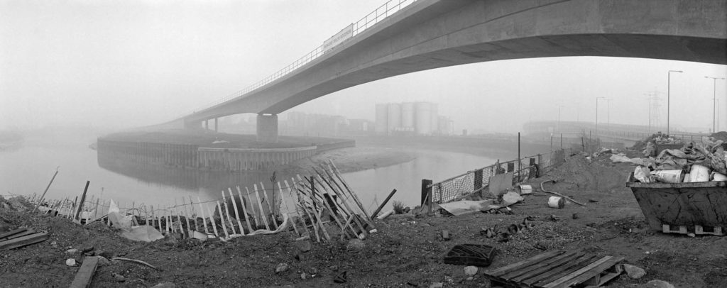 a black and white photo of a concrete bridge over river with wasteland in the foreground
