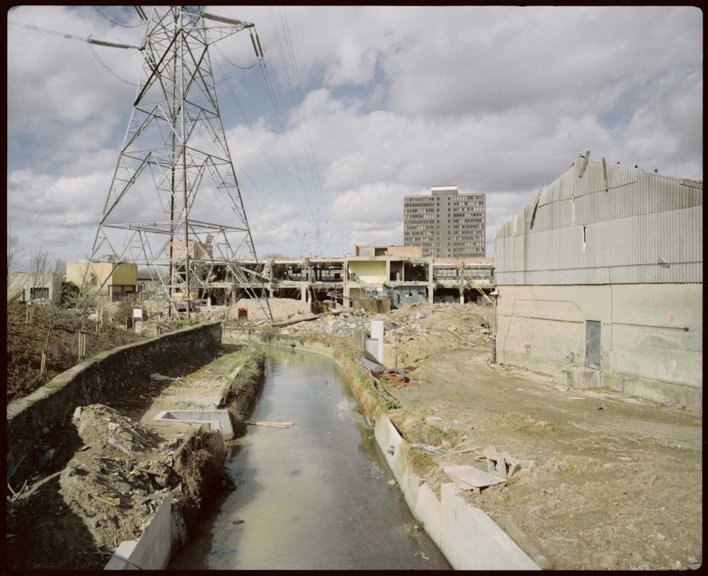 a photo of a river running through a derelict industrial site