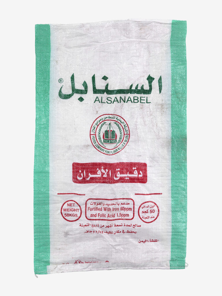 photograph of a flour sack with arabic text in red and blue, and green borders
