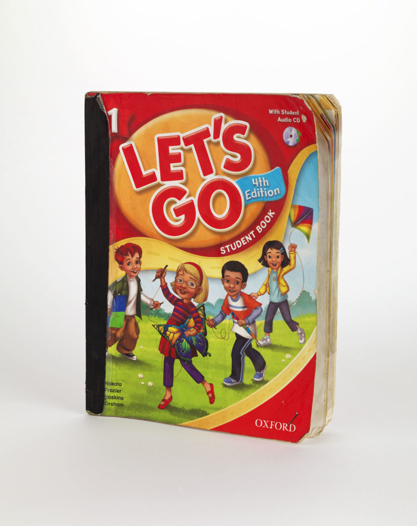 """photograph of a school workbook with title """"let's go"""" and illustrationof four children playing outdoors"""