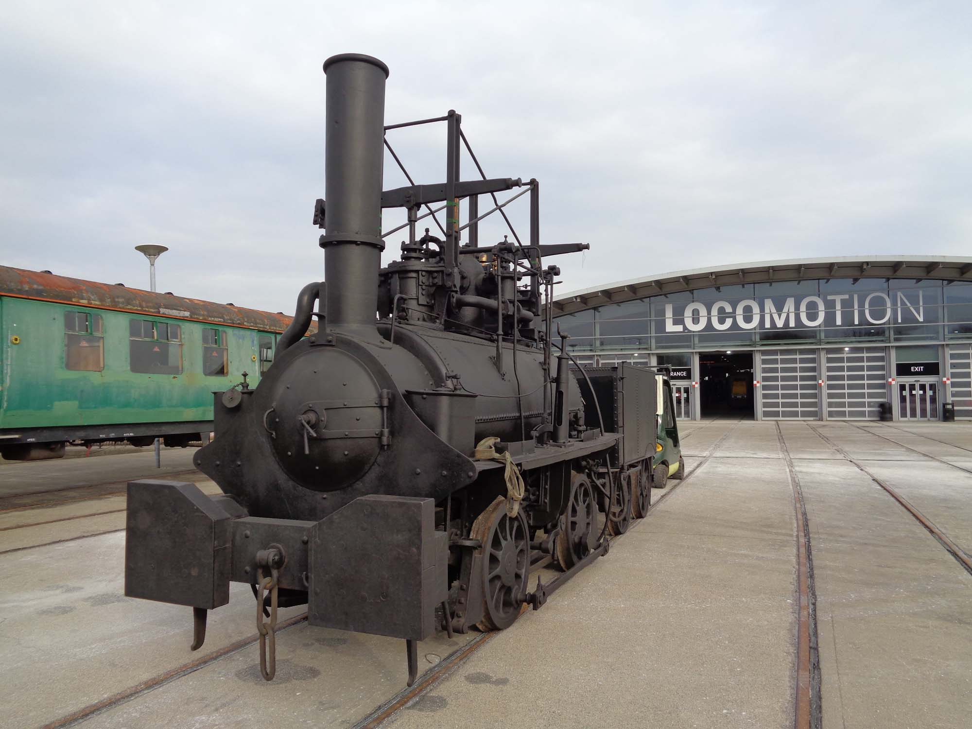 a photo of an old steam locomotive on tracks outside a shed