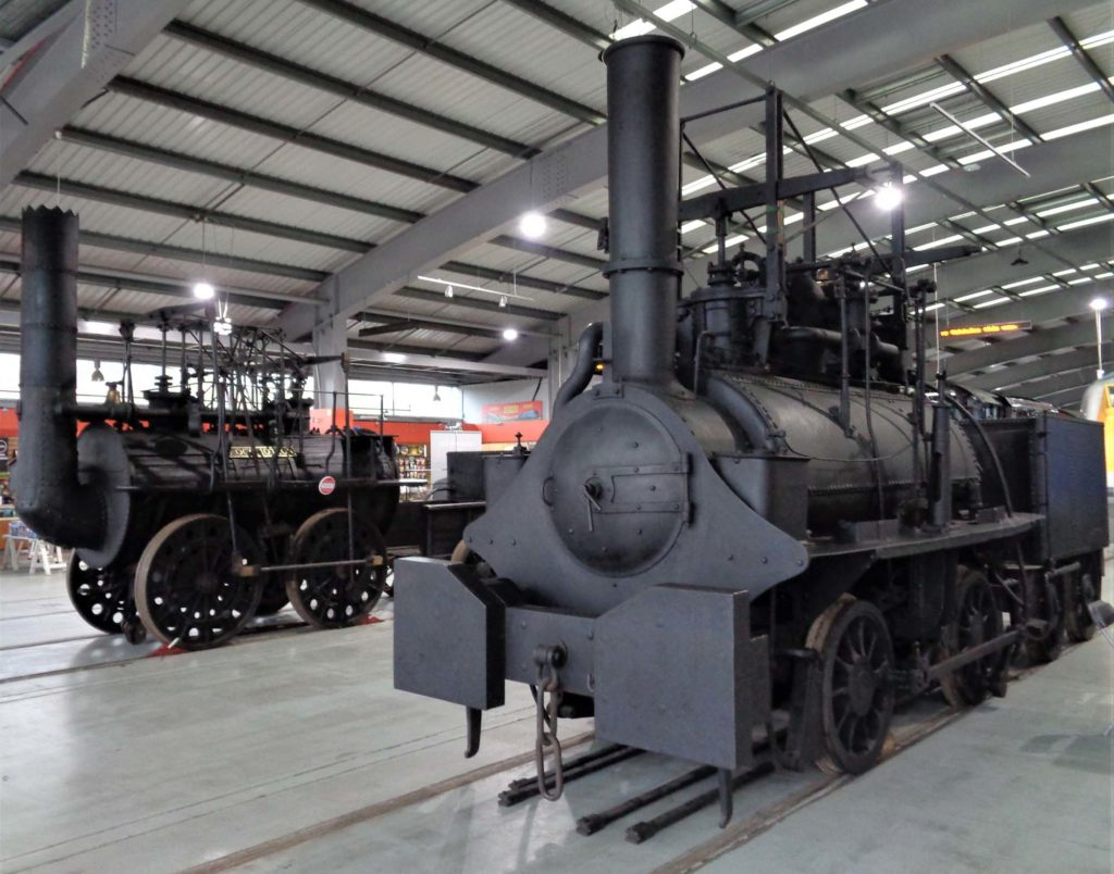a photo of two old steam locomotives side by side in a modern shed
