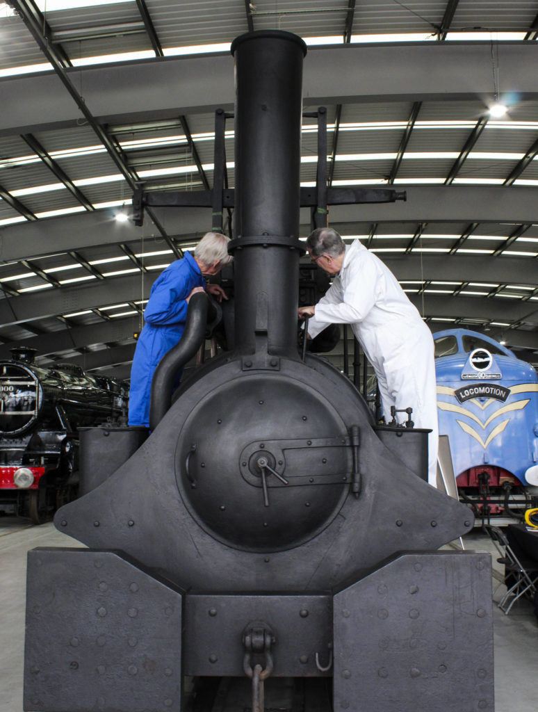 photograph of two men in boilersuits standing on a locomotive