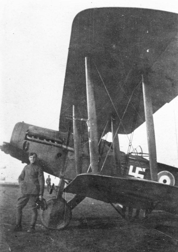 a photo of a WWI pilot next to a bi-plane
