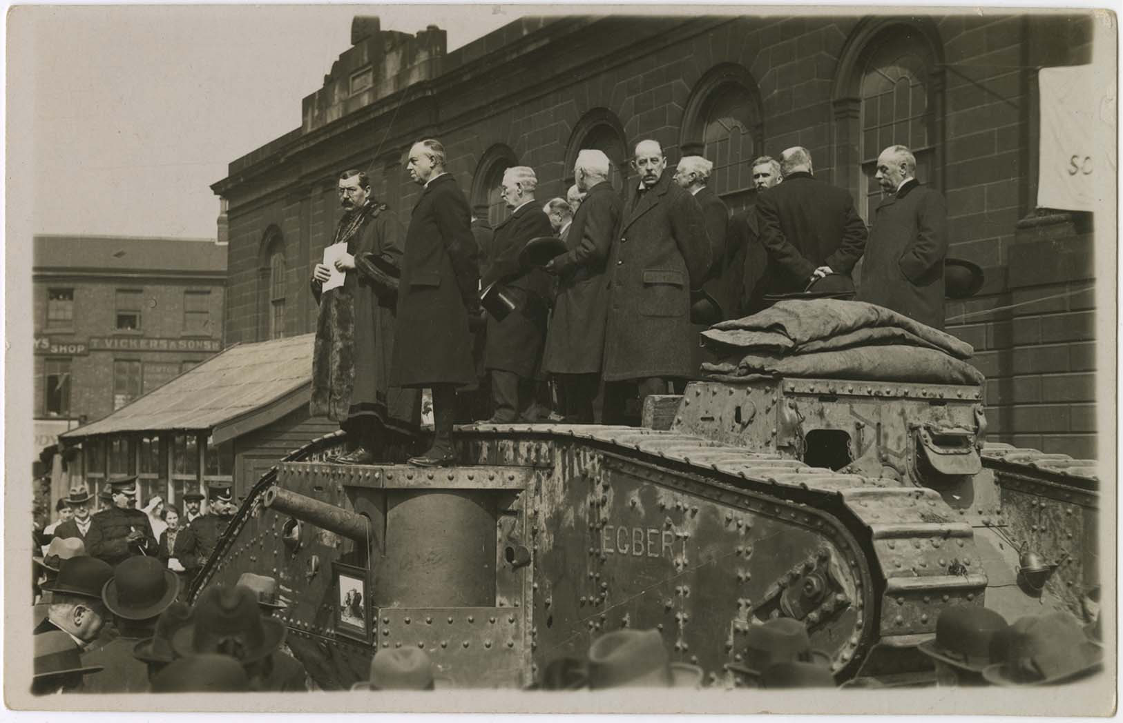 a photo of a group of men with overcoast standing on top of a First World War tank