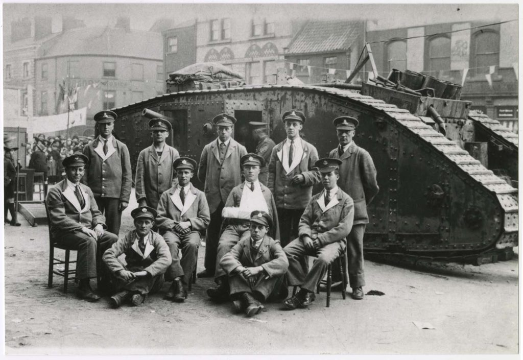 a photo of a group of soldiers in hospital blues in front of a First World War Tank