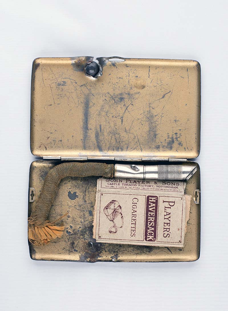 a photo of an open coiagrette case with a cigratte packets, lighter and shrapnel ball still embedded in the lid