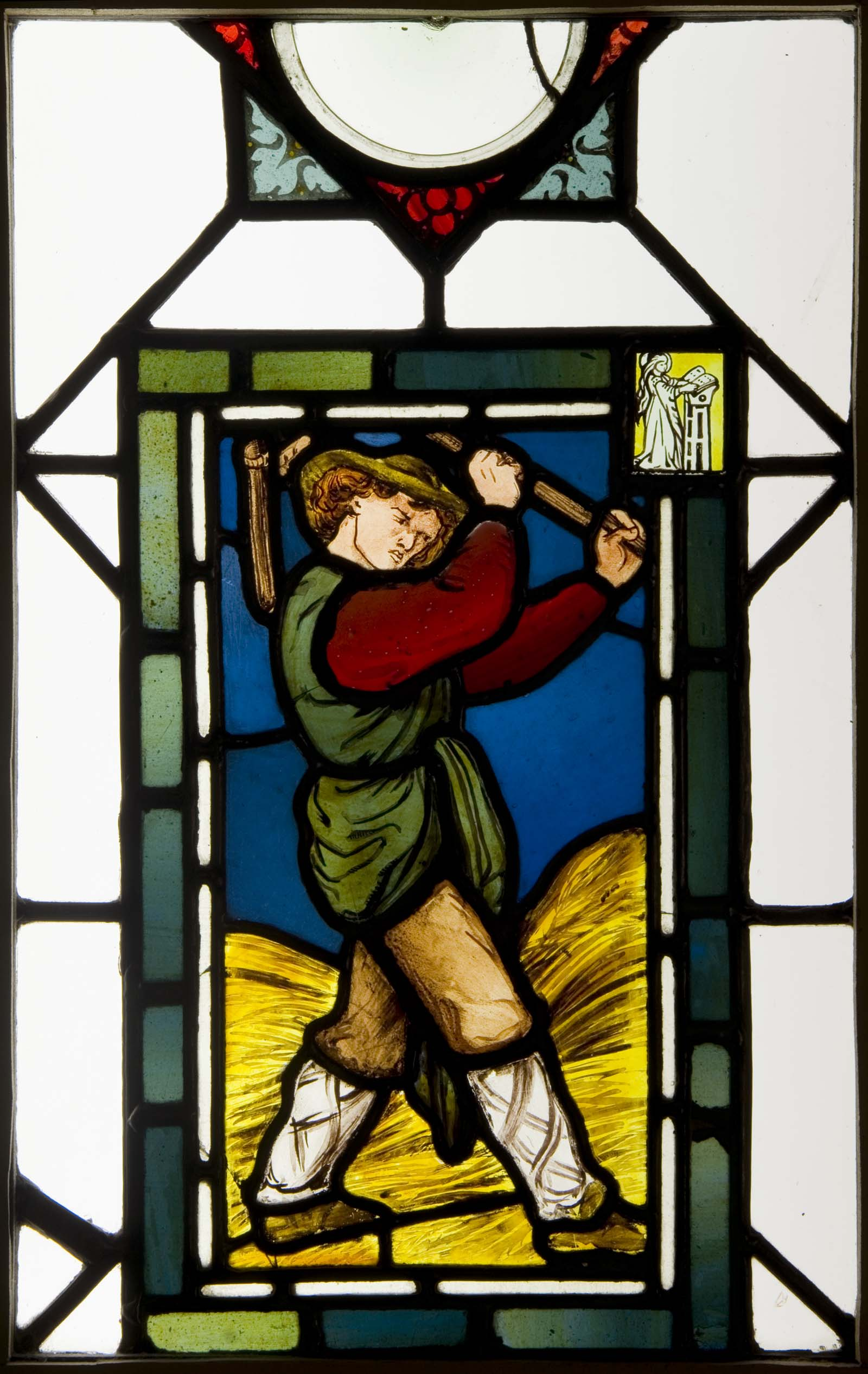a photo of a stained glass panel showing a farm labourer