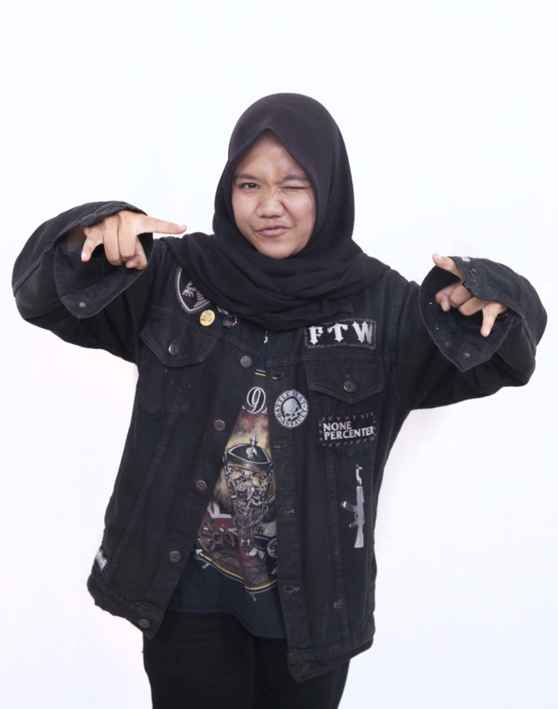 a photo of a young woman wearing a hijab and black heavy metal styled clothes