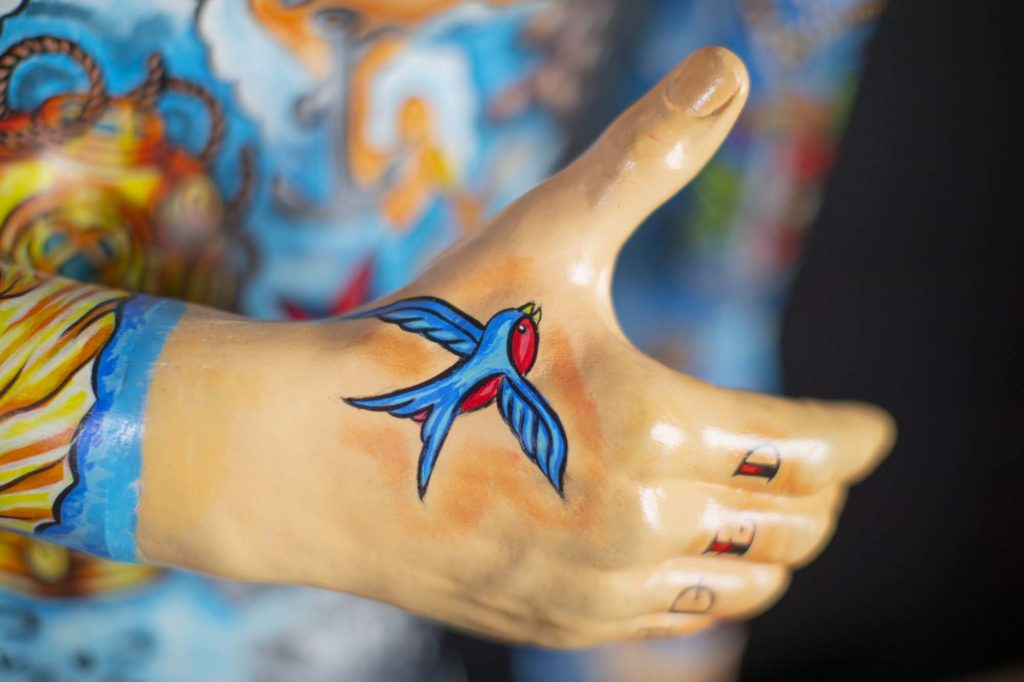 a photo of a model mannequin hand with a swallow painted on it