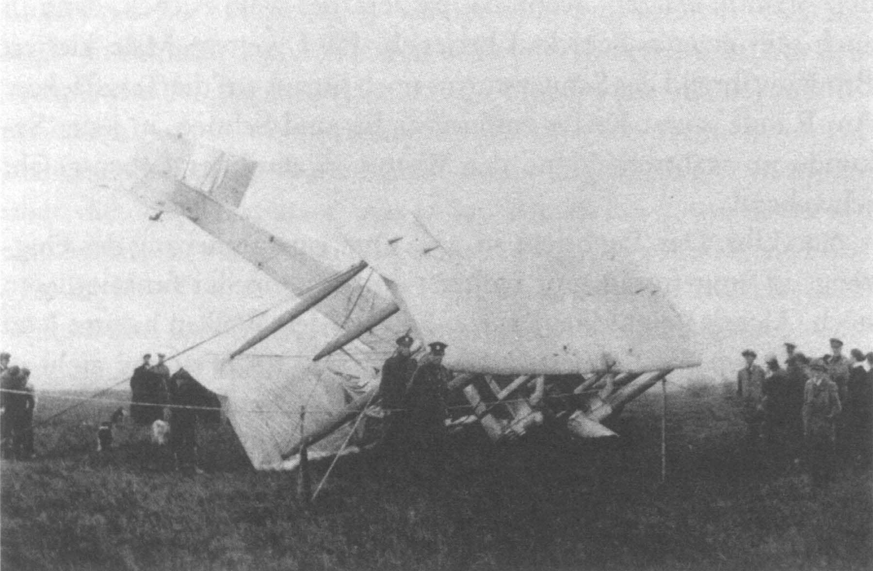 a black and white photo of a crash landed biplane with police and people stood about