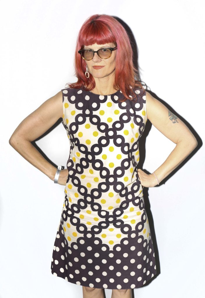 a photo of a woman with glasses and red hair and a colourful dress
