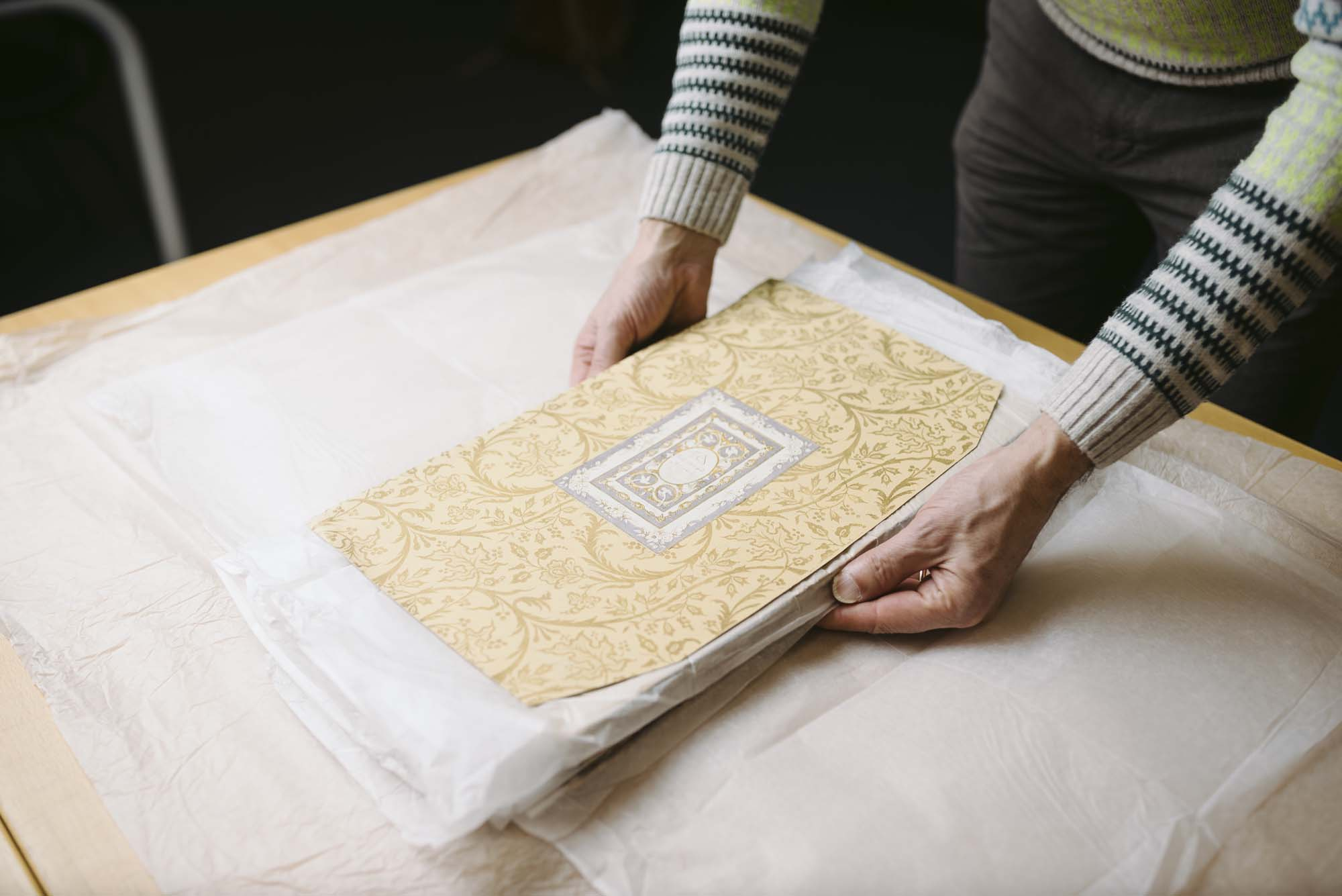 a photo of two hands holding a large pattern book
