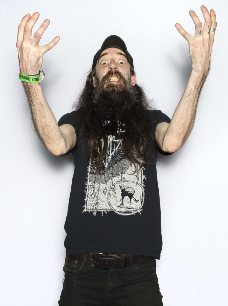 photo of a bearded dude wearing black and gesticulating with both arms raised