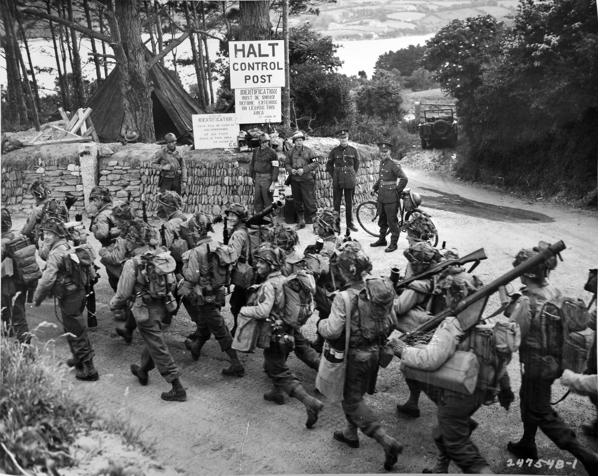 a black and white photo of US soldiers marching down a country lane past a checkpoint with sandbags and military police