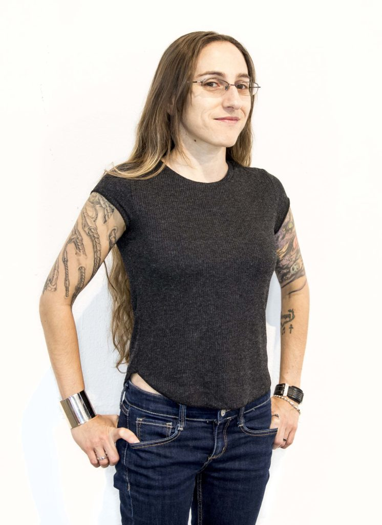 a photo of a young woman with long hair, glasses, black t-shirt, jeans and tattoos