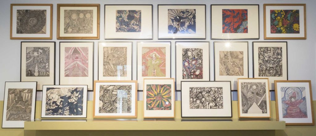 a photo of a series of prints and paintings on a wall