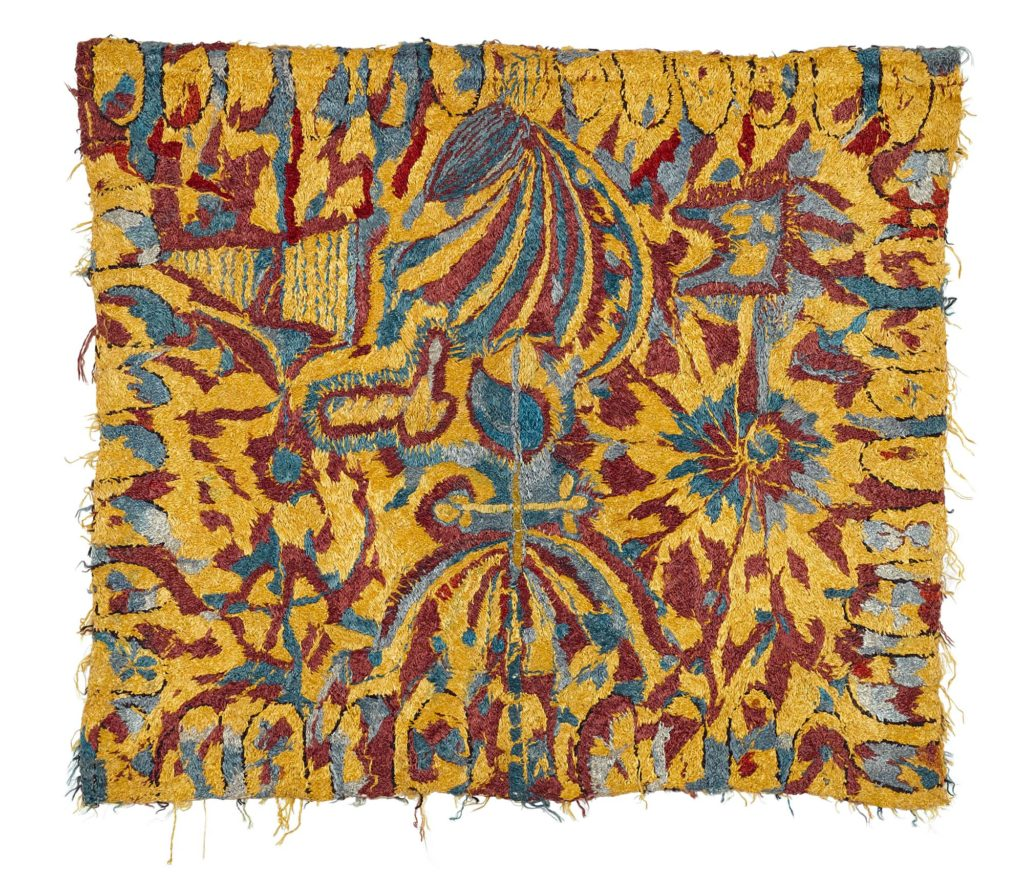 a colurful cotton embroidery with turquoise and red motifs on a yellow background