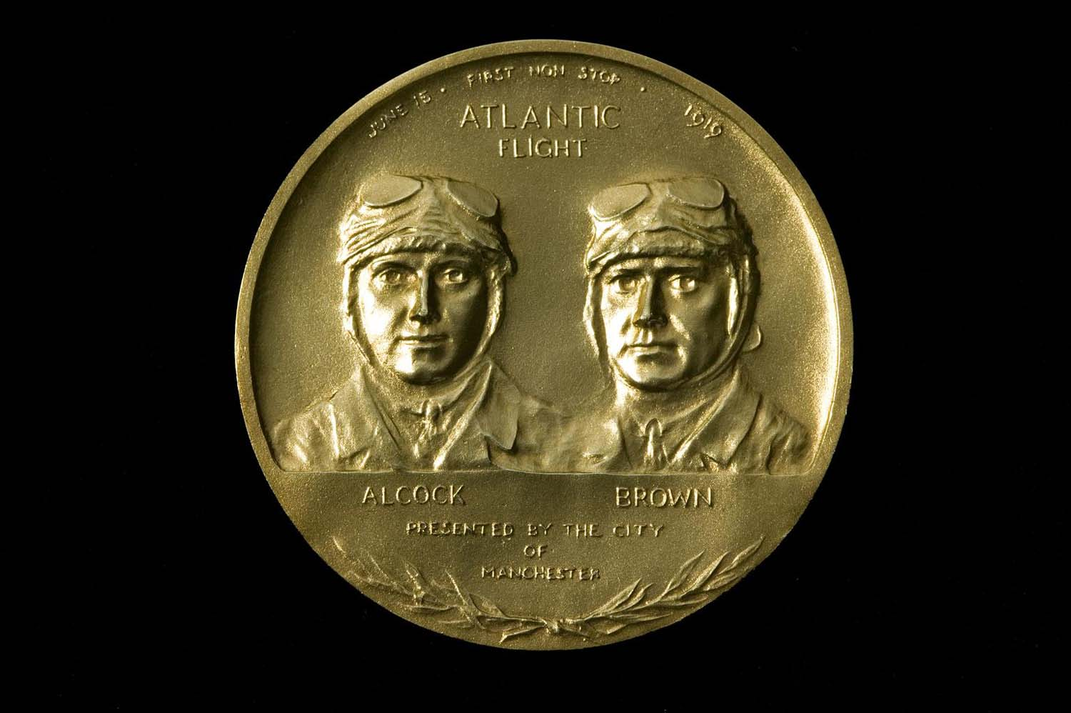 a photo of a gold medal with image of two men on its front