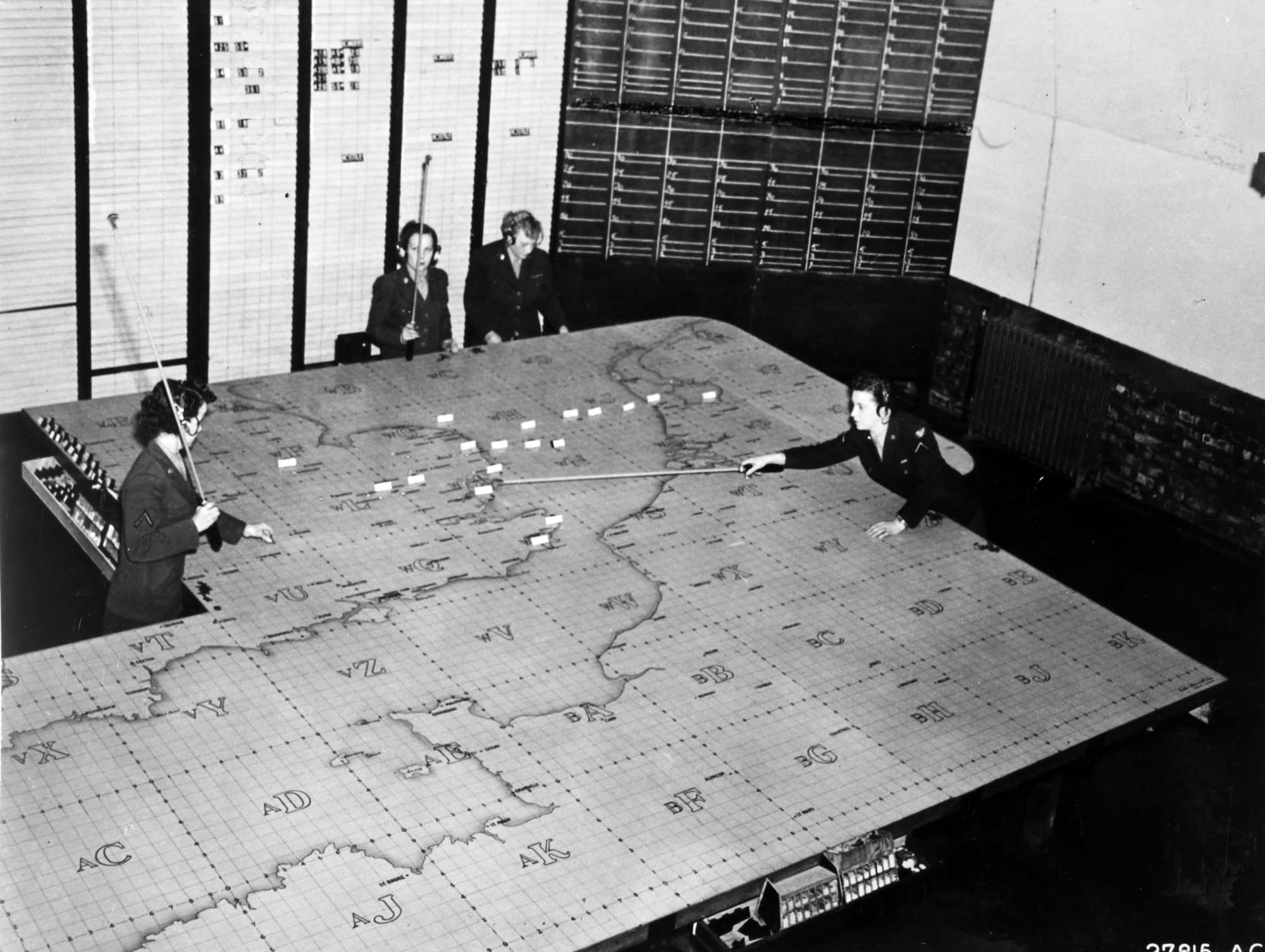 a phot of four women in unifrom moving markers around a plotting table depicting southern Britain and northern France