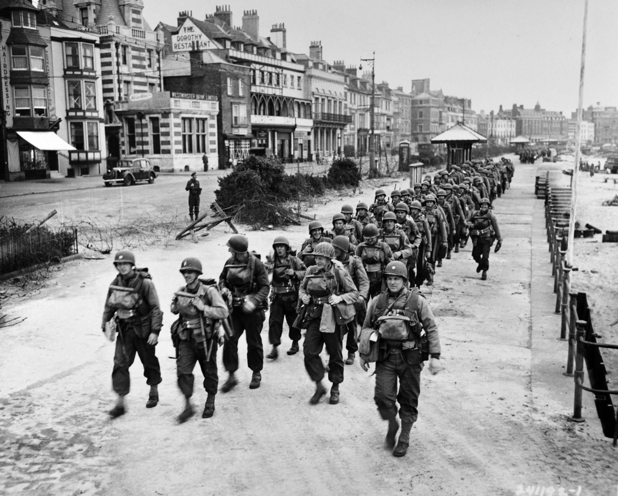 a photo of a group of US soldiers marching through a seaside town's seafront