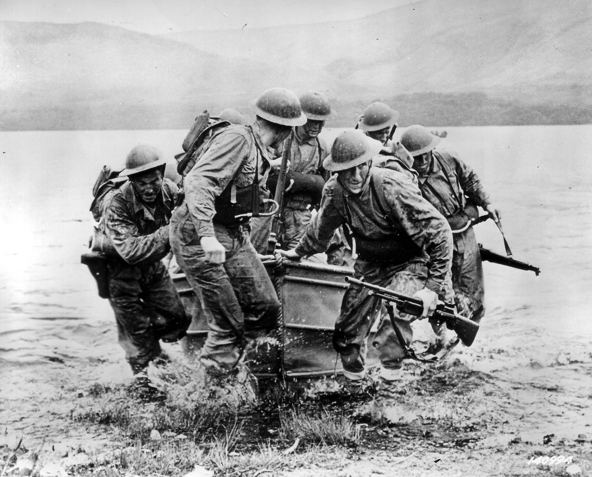 a photo of a group of soldiers bring a boat ashore on a lake