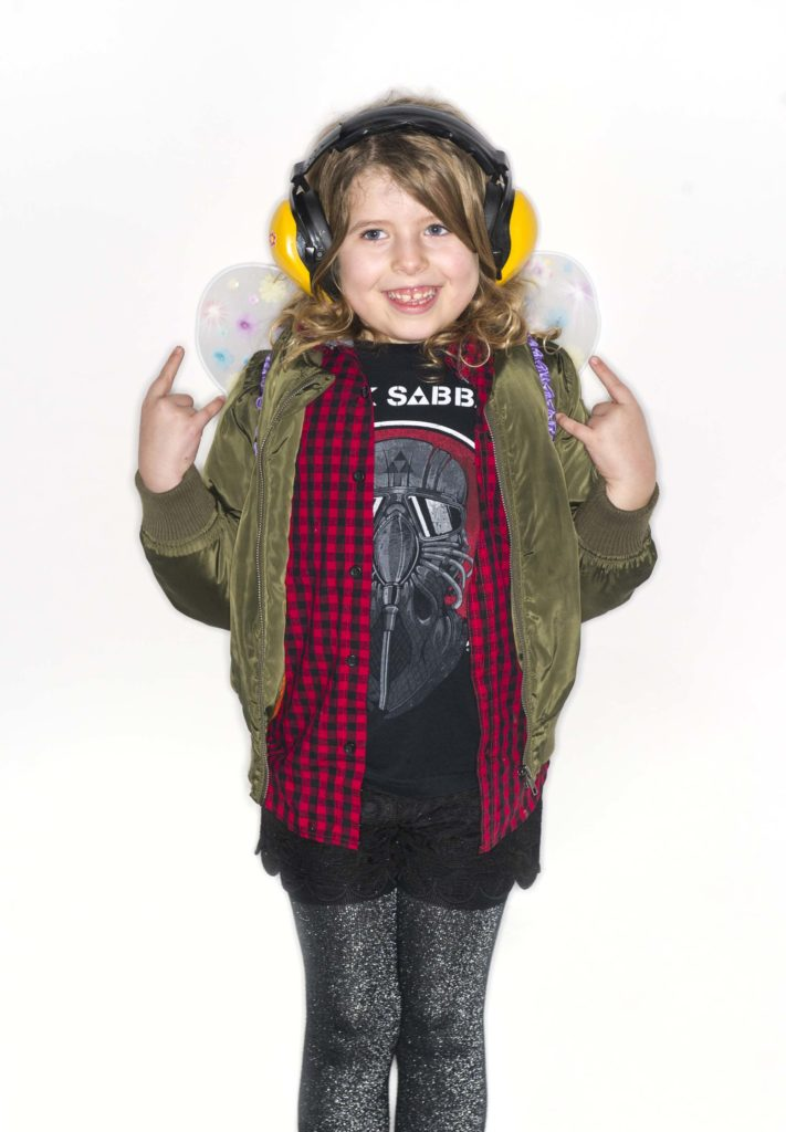 a photo of a pre-teen girl wearing ear defenders, check shirt and bomber jacket